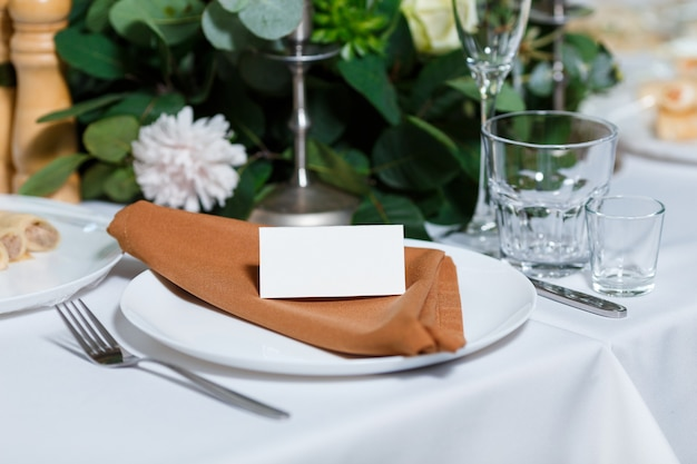 Wedding table setting with blank guest card napkin and dish on a wooden plate rustic decor
