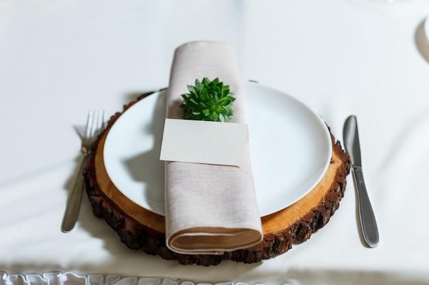 Сервировка свадебного стола с салфеткой-пустой картой гостя сочные на деревянной тарелке в деревенском стиле