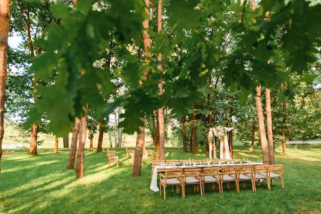 Свадебный стол с деревенским декором в лесу. празднование брака в красивом месте.