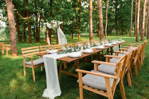 Свадебный стол с деревенским декором в лесу. тарелки и зеленая ветка со свечами на столе. зеленое украшение.