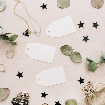 Wedding tags with eucalyptus branches, rings, stars and accessories on pale pink background. flat lay, top view