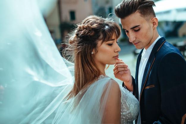 結婚式。新郎新婦は通りのクローズアップでキスします。新婚夫婦の美しいウェディングドレスとクラシックなジャケット。