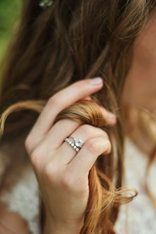Wedding theme. the hand of the bride touches her hair. hand and wedding ring