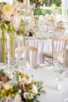 花のセンターピース、ガラス製品、食器で飾られた白いテーブルの上にスタイリッシュな装飾と場所の設定を備えた庭の屋外の結婚式場