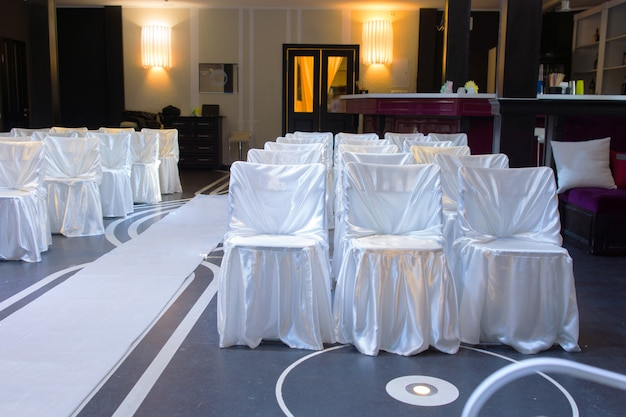 Wedding venue with decorative white chairs tied with fabric alongside a white aisle on a blue floor viewed empty from the front of the room