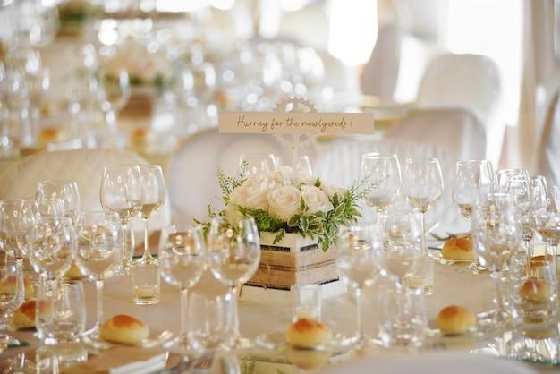 우아한 유리 제품과 작은 빵이 손으로 쓴 메시지와 함께 중앙을 감싸는 공식적인 테이블 세팅이있는 결혼식 장소