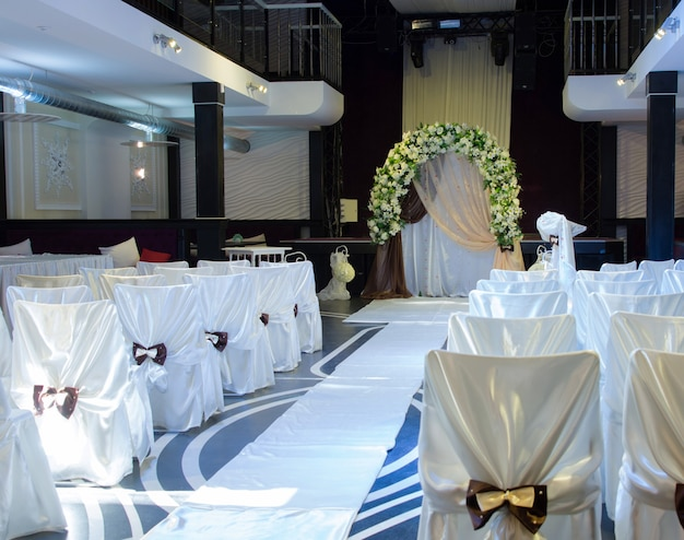 Wedding venue with a white floral bridal bower and chairs decorated with white fabric arranged along an aisle for the marriage ceremony
