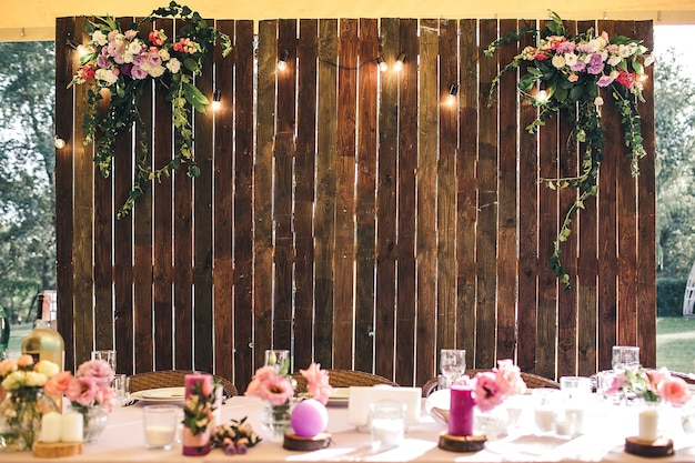 Wedding venue. wooden wall at the banquet table with lamps and flowers. copy space.
