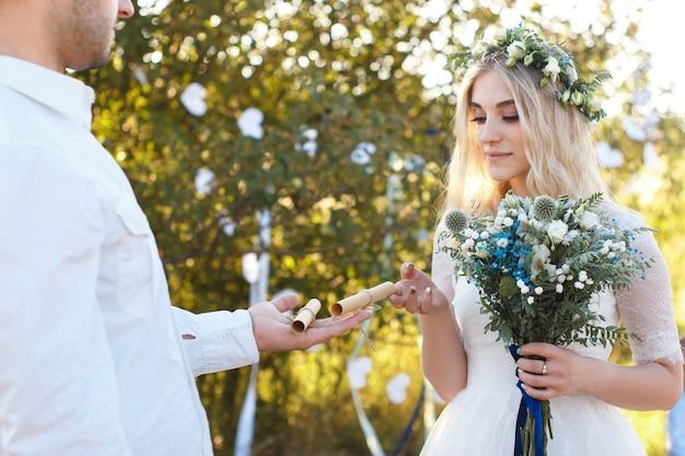 新郎の手のひらに巻かれた紙のシート、結婚式の花束、素朴な屋外の結婚式のコンセプトに結婚式の誓い。