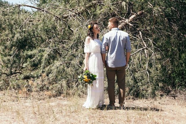 松林での結婚式の散歩。晴れた日。森の中での結婚式のカップル。散歩で美しい新郎新婦。白いウェディングドレス。牡丹とアジサイの花束。