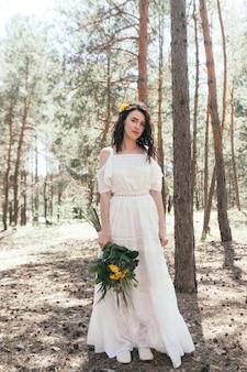 松林の中の結婚式の散歩。晴れた日。森の中での結婚式のカップル。散歩で美しい新郎新婦。白いウェディングドレス。牡丹とアジサイの花束。