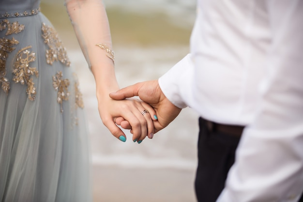 結婚式。海での結婚式。や海の背景にエレガントでスタイリッシュな青いウェディングドレスの花嫁の手を握って白いシャツの新郎。花嫁の結婚指輪の手に