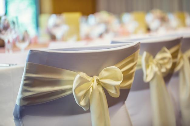 結婚式。黄金色のリボンで飾られた列の結婚式の椅子。