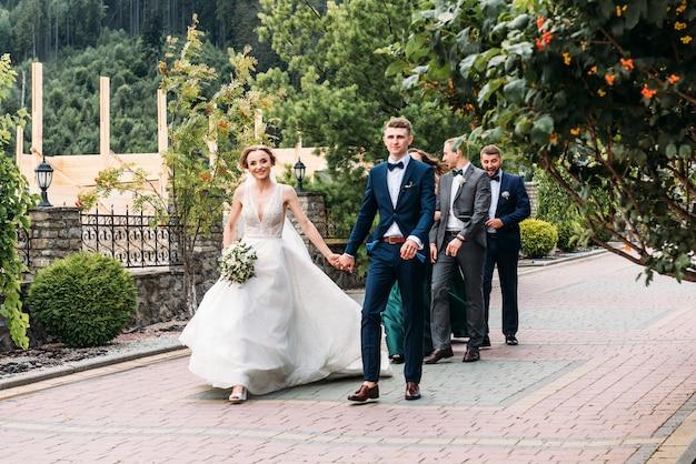 結婚式結婚式の日豪華な結婚式の後を歩く美しい花嫁とエレガントな新郎