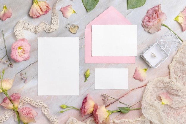 Свадебный свадебный набор канцелярских товаров с конвертом на мраморном столе, украшенном цветами и лентами. макет сцены с пустыми бумажными поздравительными открытками. женственная плоская планировка