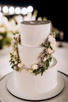 緑の装飾が施された白い表彰台の近くの高いスタンドで結婚式の白いケーキ