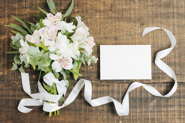 Wedding white card and peruvian lily flower bouquet tied with ribbon on wooden desk