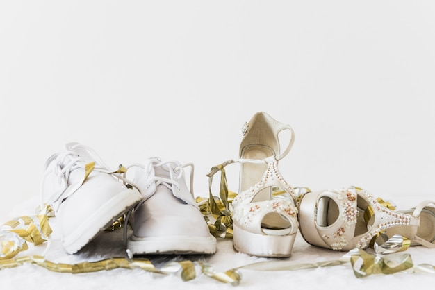 Wedding white shoes and elegance high heel with golden streamers on white background