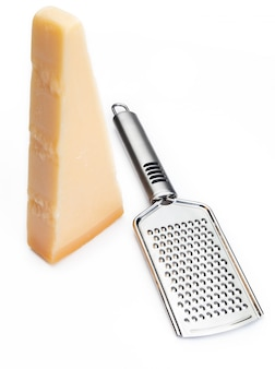 Wedge of parmesan cheese or grana with grater.