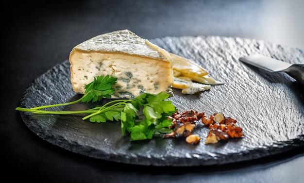 ローアングルで見たナイフで円形の黒い木の板に刻んだクルミと新鮮なパセリとおいしいブルーチーズのくさび部分