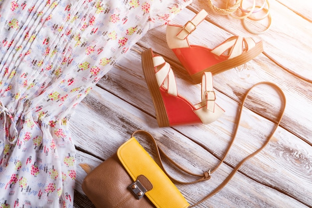 Wedge sandals and bicolor purse. colorful bracelet set with bag. woman's summer footwear on display. clothing and accessories.