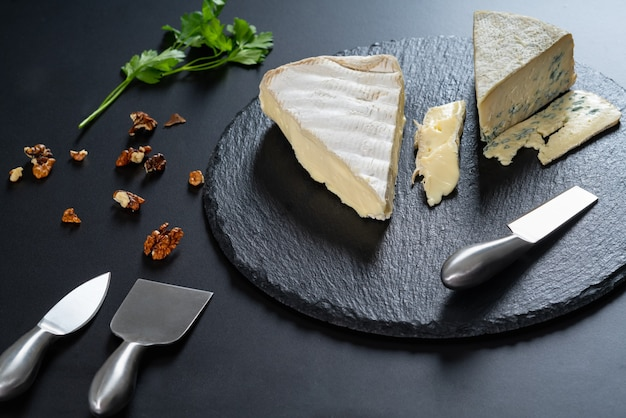 スチールカッターと散らばった刻んだクルミを使った黒い木製のチーズ盛り合わせにセミソフトチーズのくさびを入れて、ハイアングルの食品静物画に