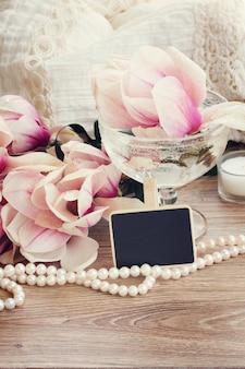 結婚式の挨拶-黒いチョークボードにコピースペースのあるマグノリアの花と真珠のストランド