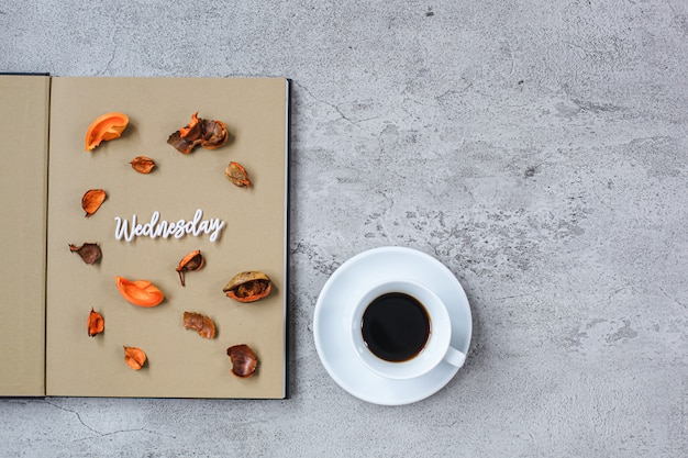 Wednesday flat lay minimalist autumn concept with book and a cup of coffee on grey cement background