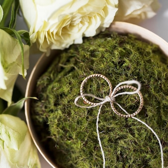 Weeding rings tied with strings on moss put with roses