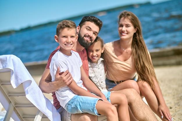 주말. 물가에서 시간을 보내고 여유로워 보이는 행복한 가족
