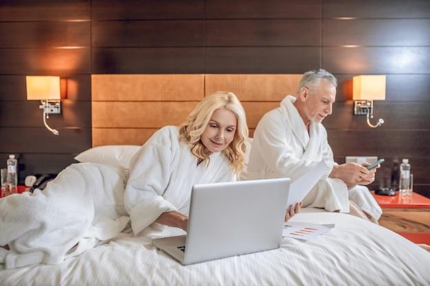 주말. 편안한 호텔에서 하루를 보내는 목욕 가운의 커플