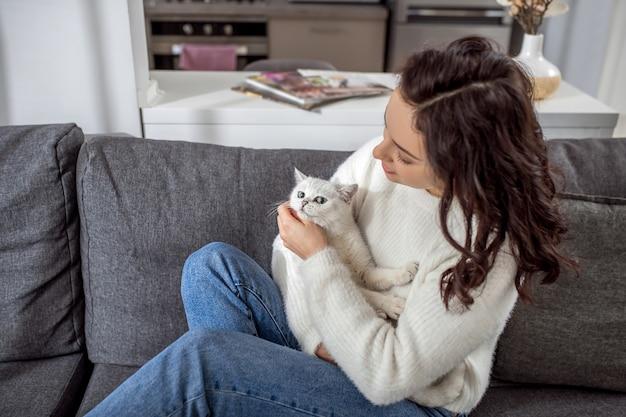 週末。彼女の猫と家で週末を過ごすかわいい若い女性