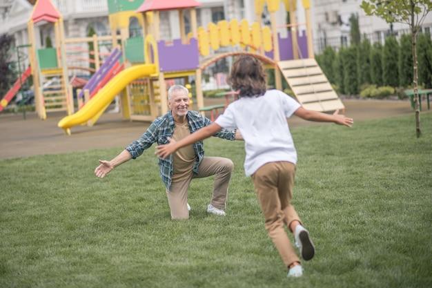 Выходные, папа. мальчик бежит к своим отцам с распростертыми объятиями и выглядит счастливым