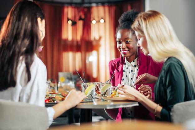 週末のディナー 3 人の親友が伝統的な週末のディナーを一緒に楽しみながら興奮している