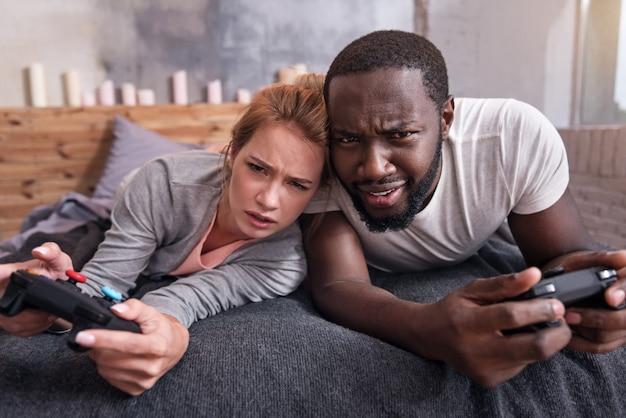 Развлечения выходного дня. веселая молодая пара из разных стран играет в видеоигры и лежит в спальне, проводя время вместе
