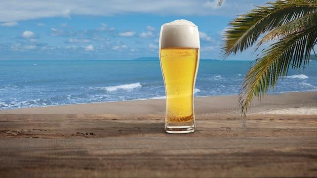 주말. 야자수와 하얀 모래가 배경에 있는 바다 또는 바다 해변과 함께 햇살 아래 시원한 맥주와 유리. 나무 테이블에 전통적인 알코올 음료입니다. 여름, 휴가, 리조트, 냉기의 개념.