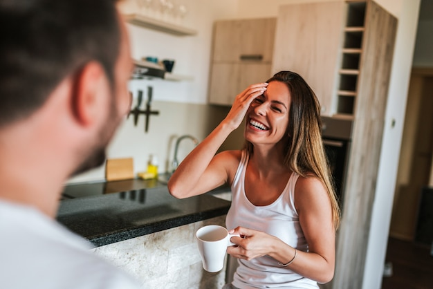 Weekend morning. couple laughing while having coffee in the kitchen.
