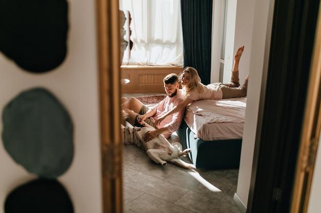 밝은 침실에서 래브라도 놀고 부부의 주말 사진. 남자와 여자가 큰 개의 배를 쓰다듬고 있습니다.