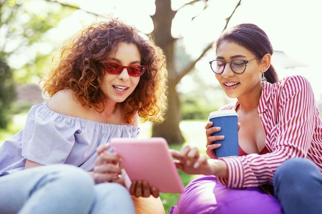 一緒に週末。タブレットを持って友達と話している格好良いインスピレーションを得た女性