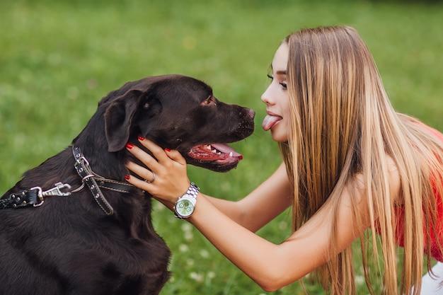 公園で犬との週末。彼女のペットを持つ女性。