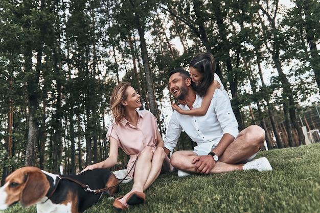 주말 가족과 함께. 공원의 잔디에 앉아 웃고 있는 3명의 행복한 젊은 가족