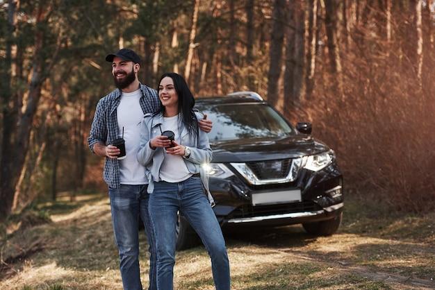 주말 시간. 자연을 즐기고 있습니다. 부부가 새 검은 차를 타고 숲에 도착했습니다.