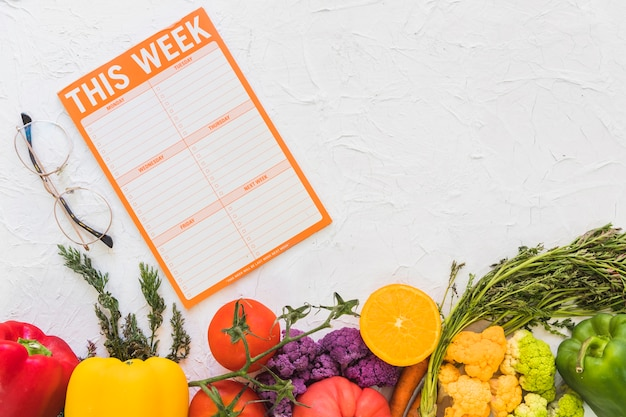 Weekly meal plan with colorful fruits and vegetables on textured background