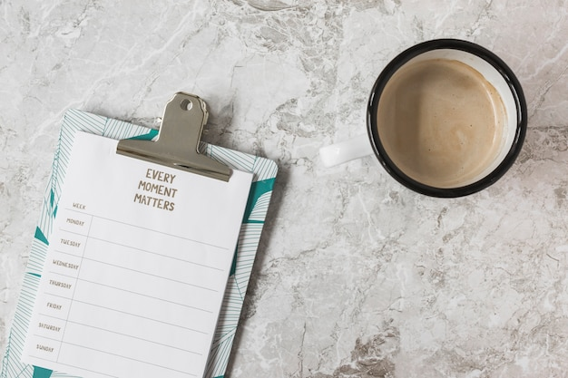 Weekly plan on clipboard and cup of coffee over the marble backdrop