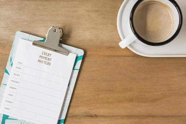 木製の机のクリップボードとコーヒーの1週間の計画