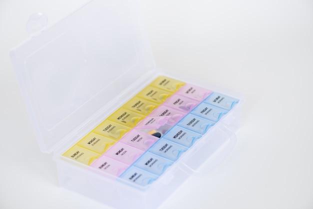白い背景の上の丸薬と毎週のプラスチック製の丸薬オーガナイザー