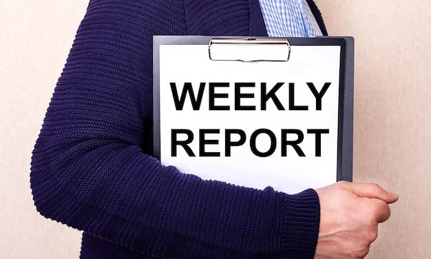 Weekly reportは、横に立っている男性が持っている白いシーツに書かれています