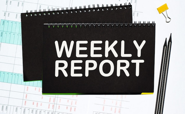 'weekly report' notebloc, pen and clip on the desktop. business concept.