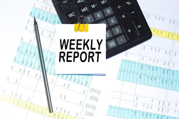 주간 보고서 텍스트, 계산기 및 펜이 바탕 화면에 있습니다. 계산기와 펜. 비즈니스 개념입니다.