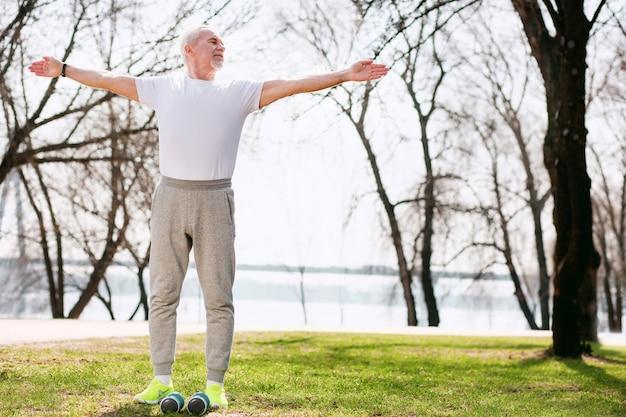 Еженедельная тренировка. довольный зрелый мужчина работает в парке и движется руками